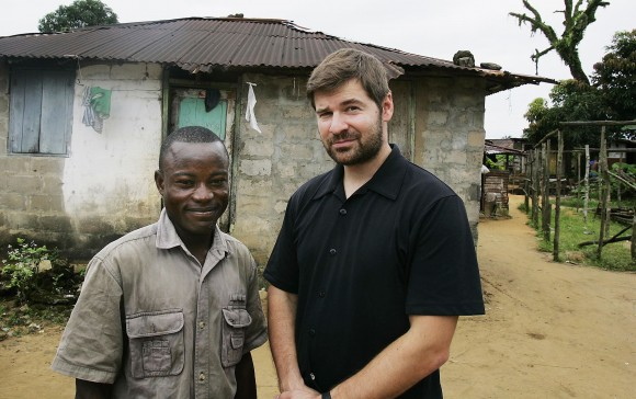 "MONROVIA, LIBERIA - OCTOBER 05:  Joseph Duo (L), 28, a former Liberian government soldier, poses with photographer Chris Hondros at his home October 5, 2005 in Monrovia, Liberia.  A picture of Duo jumping into the air in exultation during a battle with rebel forces in 2003 was distributed around the world, making him a symbol of the intractable difficulties of Liberia's long civil war. Duo, now de-commissioned by the United Nations and unemployed, lives in a squalid neighborhood on the outskirts of Monrovia with a wife and three children, but his fame lives on. He's well known among Monrovians and is often stopped by people who recognize him from the photo. He is unapologetic about his military career, which began at the start of the Liberian civil war in 1990, when he was 14. ""You have to adapt yourself to the system, and that's the system I found myself in,"" he says, ""I fought in the interest of the people."" (Photo by Getty Images)"