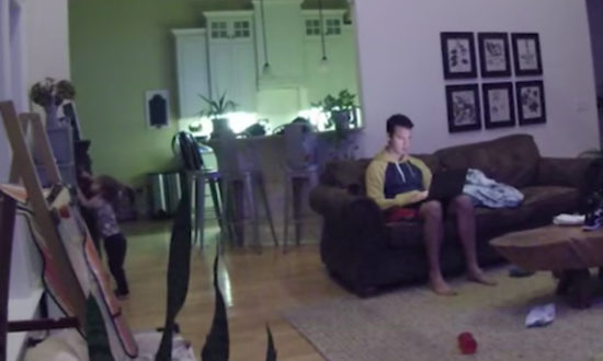 Toddler wonders into room, but when he gets to the bookshelf—just watch the dad